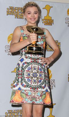 Dressed in an intricate tapestry style dress with black stilettos, Chloe Grace Moretz dazzled as she wins Best Performance by a Younger Actor at the Saturn Awards http://dailym.ai/1lwBx1d