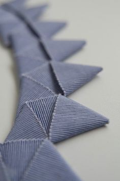 Ribbon Folding fabric manipulation technique - fabric origami; inspiration for decorative trims or textured surface pattern design.  I love this as a neckline trim.