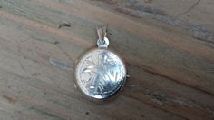 pretty round sterling silver locket (no chain) engraved on both sides. 2.5 cm in length and depth of 60mm