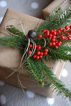 Festive and natural Christmas gift wrap. Kraft paper, twine and sprigs of evergreen and red berries. Tie it together and accent with a jingle bell.