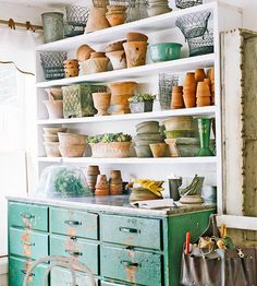 Found Order - escued from the trash and hung high on a wall, a bookcase offers long, shallow shelves ideal for organizing garden containers. Below the bookcase stands a dresser. The top of the dresser was wrapped with tin, which allows the piece to function as a convenient potting bench.