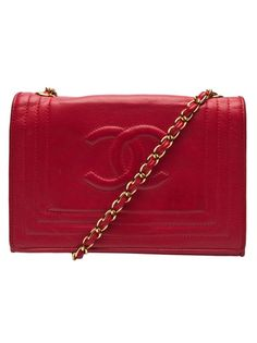 Chanel small flap bag in red from Chanel vintage. This vintage lambskin leather handbag features a top flap with magnetic snap button closure, large embossed logo on front with frame stitching, and a long leather and gold chain shoulder strap. Has an interior zipper pocket, and comes with a card of authenticity. measures 5.5