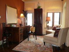 The second floor office, fit with a whiteboard and desk, features a tall antique Chinese cabinet for added effect.