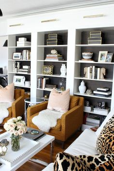 ILLINOIS LIVING ROOM DESIGN | Kristin Cadwallader | leopard pillows | blush | black and white | grasscloth backed bookcases | Ikea Billy bookcase hack | modern meets traditional | brass library lights