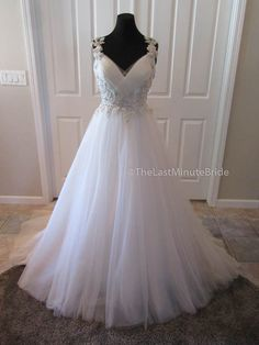 Description The ultimate feminine dress. Dreamy layers of tulle make up this A-line wedding dress. The dress features a V-neckline with pleated tulle bodice. Gorgeous embroidered floral straps and det