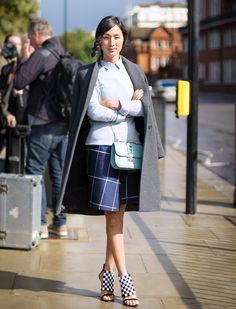 Grey coat, light blue button down and sweater, blue skirt, blue bag, and checkered heels