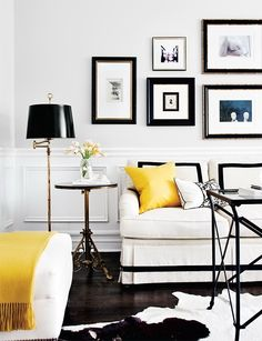 Irene Langlois - Black & yellow living room with chair rail & wainscoting, art gallery, white skirted William Birch Sofa with black ribbon trim, canary yellow pillow & throw, antique brass pedestal accent table, antique brass swing-arm floor lamp, black & white cowhide rug, glass-top directoire table and white ottoman.