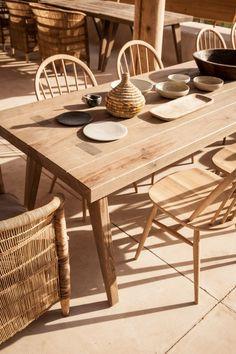 Esstisch, Stühle und traditionelles Geschirr aus Naturholz und Schilf
