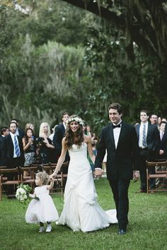 Adorable image of couple exiting wedding ceremony with their daughter, photo by Richard Israel | junebugweddings.com