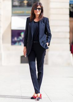 Emmanuelle Alt adds a touch of color to her black suit with a pair of bright red heels