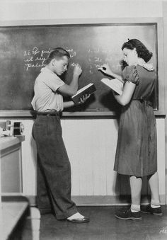 Mickey Rooney and Judy Garland practice writing out their Spanish in a class at MGM's studio school.