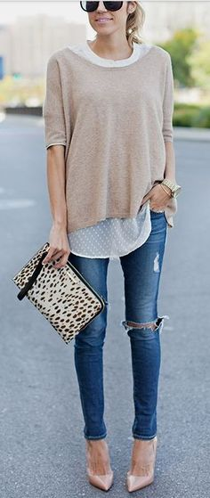 Ripped skinny jeans, a flowy top and sweater, nude heels, and a printed clutch.