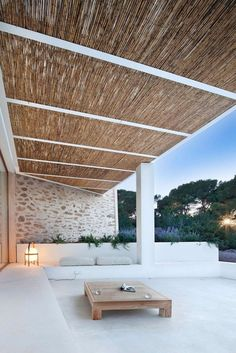 This relaxing, covered outdoor space has built-in seating, a light stone wall, and a bamboo roof.