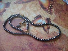 Conjunto de composto de colar,pulseira e brincos. Confeccionado em contas tipo pérola, cor grafite e acabamentos em metal dourado. Medida do colar: 44 cm de diâmetro. Pulseira: 20 cm de diâmetro. Brincos: 2 cm de comprimento.