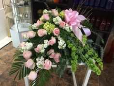Pink roses, white stock, bells of Ireland & pink bow casket spray by Donna Jeffries