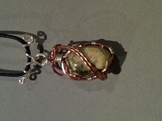 Silver and copper wrapped pebble close up