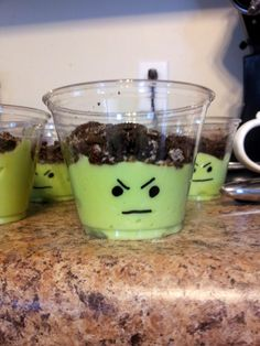 Vanilla pudding with green food coloring...  Topped with crushed oreos.  Draw on clear cup with black sharpie.