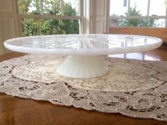 This footed lovely milk glass cake stand has a wonderful starburst pattern design. Pretty scalloped edge and fluted edge base. Bright white. It is in wonderful vintage condition. Nice smaller size. Great for serving at home or at your party celebration. Turn it over for use with a candle. Also wonderful for use on the vanity, displaying small plants, mini frames or anything you want to give a lift to.  Approximate measurement: 10.25 by 2.5 high