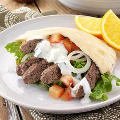 Ground Beef Gyros Recipe -If your family likes gyros as much as mine, they'll love this easy version that's made with ground beef instead of lamb. I found the recipe in a newspaper and adapted it to fit our tastes. They're very much like the ones served at a local restaurant. A cucumber yogurt sauce adds an authentic finishing touch. —Ruth Stahl, Shepherd, Montana