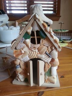 """Diy Fairy House/Cottage """"Conch Cottage"""" made with tumbled shell pieces accented with sea glass.  It all started with a bird house, squared out the round hole at the top to resemble a window. Still a work in progress."""