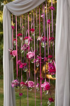 flowers in vases hanging from ribbon backdrop