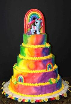 5 tier rainbow cake for my daughters 4th birthday. Iced in airbrushed buttercream with gumpaste rainbows. The pony is a toy (sigh)...my da...