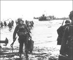 The Normandy Invasion: The Story in Pictures  Invasion. Carrying a full equipment, American assault troops move onto Utah Beach on the norther coast of France. Landing craft, in the background, jams the harbor. 6 June 1944. Photographer: Wall. SC189902