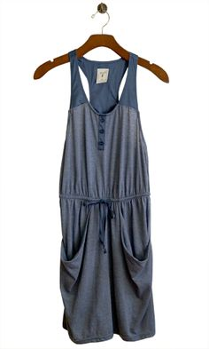 Play all day in this casual yet stylish romper. The sand and surf hue gives a vintagey feel to the softest, most perfect cotton jersey knit to keep you cool all summer long. Fun floppy front pockets with satin button front tabs, tank front, racer back and waist tie.