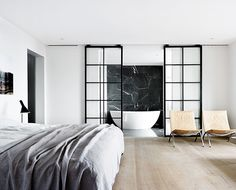 Nice bedroom, don't you just love that grey linen bed cover? And those gorgeous black sliding doors leading to an even better bathroom. Wow, that black bathroom wall!