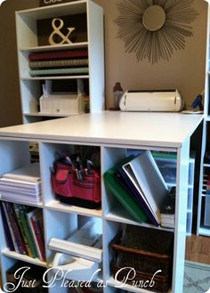 DIY craft table - check out the bookshelf - it's got holes up and down on each side, add a down rod and you can hang your wrapping paper or ribbons on dow rods. Genius.