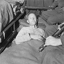 "William Joyce, who was ""Lord Haw-Haw"" to British wartime listeners, now silenced and under arrest, lies in an ambulance under armed guard before being taken from British Second Army Headquarters to a hospital."