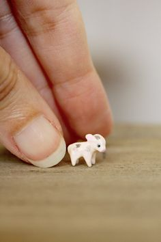 This handsculpted tiny piglet is just 11mm (less than half an inch) long!  Its been handsculpted from supersculpey clay, and has the tiniest glass eyes. The piglet has been baked and painted with several layers of acrylics, to achieve perfect coverage and smoothness - and then carefully checked to ensure its cuteness before glazing it. Transparent varnish has been applied applied for maximum shine and durability.  And it will come in a cute tiny box, ready for gift giving or for joining…