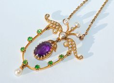 Pendant in the Suffragette Colors  Circa 1910 -   A high-carat gold pendant set with an amethyst, rare green demantoid garnets and natural pearls. The colors are those of the Women's Suffragette movement, symbolizing green for hope, white for purity and purple for regal dignity.The pendant measures 4 cm by 3 cm [1 and 2/3 inches by 1 and 1/4 inches] and the chain is 18 inches long. A rare Suffragette piece in immaculate condition in its original case.