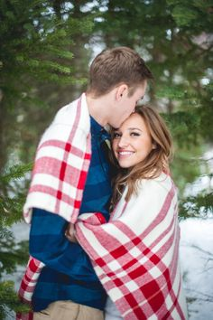 Bundle up in a flannel blanket for a cold engagement shoot in the mountains. I love the color contrast of the pine trees with the blue and red