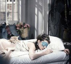 chica acostada en una cama usando un antifas para dormir mientras el gato esta sobre ella