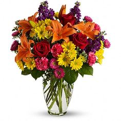 Bright Eyes - [T528-1A]  Start the party with a spectacular blend of red roses, orange lilies, purple stock, pink asters and more in a classic clear glass vase. Whether it's a birthday, anniversary or any special occasion; be sure to invite this fun, fabulous bouquet.