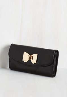 Keep your essentials secure within the fancy flair of this black, vegan-friendly wallet! High-gloss faux leather, a gold bow closure, and a roomy, pocketed interior give this piece a surplus of posh style that makes organizing your necessities a newfound joy.