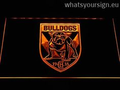 Canterbury-Bankstown Bulldogs - Neon sign LED display made of the first-class quality transparent plastic and glowing colorful illumination. The neon sign displays exactly the same from every angle thanks to the carving with the modern 3D laser engraving technology. This LED neon sign is a great gift idea! The neon is provided with a metal chain for displaying. Available in 3 sizes in following colours: White, Purple, Orange, Yellow, Red, Green and Blue!