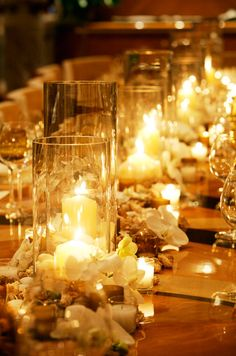 A bright orange glow emanates from pillar and votive candles that light the center of a long rectangular reception table.