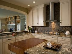 The combination of earthy tones and textures of the granite countertop, slate backsplash and green walls creates a harmonious look that is inviting and peaceful kitchen.