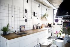 Wood counter + plants warm up a white industrial kitchen