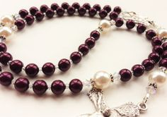 Such a beautiful rosary in a unique deep blackberry plum! The Hail Mary beads are of Swarovski pearls in deep reddish plum, with Our Father beads in contrasting white. Very striking! Accented with genuine Swarovski crystals, this rosary would make a beautiful and very classic gift or a beautiful choice for personal use.  This rosary is pictured with a rose centerpiece. However, I do have other centerpieces available! If you prefer a different centerpiece with this rosary, please message me…