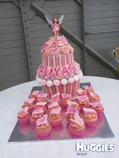Strawberry and Vanilla sponge two tier giant cupcake held together with white chocolate icing. Decorated with pink buttercream roses, purple sugar pastes pansies, musk stick lollies, white chocolate biscuit sticks and pink and white marshmallows. Topped with pink sugarpaste edible glitter name, age and 3 butterflies with a fairy on top. When the cake is cut out spill hundreds on smarties! Surrounding the cake are mini vanilla and pink buttercream cupcakes topped with fondant butterflies by…