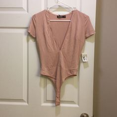 V neck bodysuit Pale pink NWT thong vneck bodysuit. Buttons in the crotch area for ease. Super cute! Necessary Clothing Tops