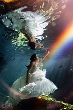 Magic can happen in the sacred cenotes of the Riviera Maya, natural light creating a rainbow for this mermaid bride in her trash the dress shoot. Mexico wedding photographers Del Sol Photography.