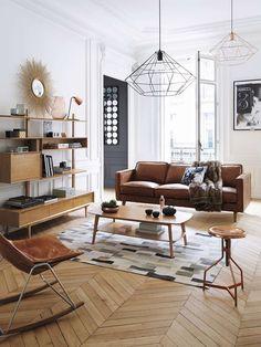 Salón con sofá en cuero, muebles en madera y detalles en metal