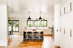 White kitchen with black accents and shiplap walls