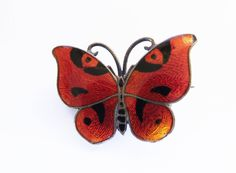 Butterfly Brooch Orange Enamel Rare CG Hallberg Guilloche 1921 Sterling Silver Stockholm A very Rare Guilloche Enamel Butterfly Brooch/pin from **CG HALLBERG. Gorgeous Orange and Black Butterfly with black body and sterling antenna. There is a little gradation to the colors, original to the pin. It Is Marked HALLBERG, and hallmarked for Stockholm, Sterling and 1921. It has a simple C and Hinge pin clasp. Measures 7/8 x 5/8.