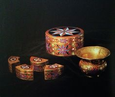 Engraved gold betel leaf and areca nut box with agate top decorated with multi- colored stones and a set of small matching  boxes. A gold and enamel spittoon.
