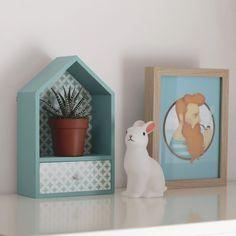 Estantería de madera con forma de casita en color azul. Quedará genial en tu hogar dándole un toque de color y alegría.  Incluye ganchos para colgarla en la pared y un pequeño cajón para almacenaje. La trasera y el cajón están adornados con papel decorativo.